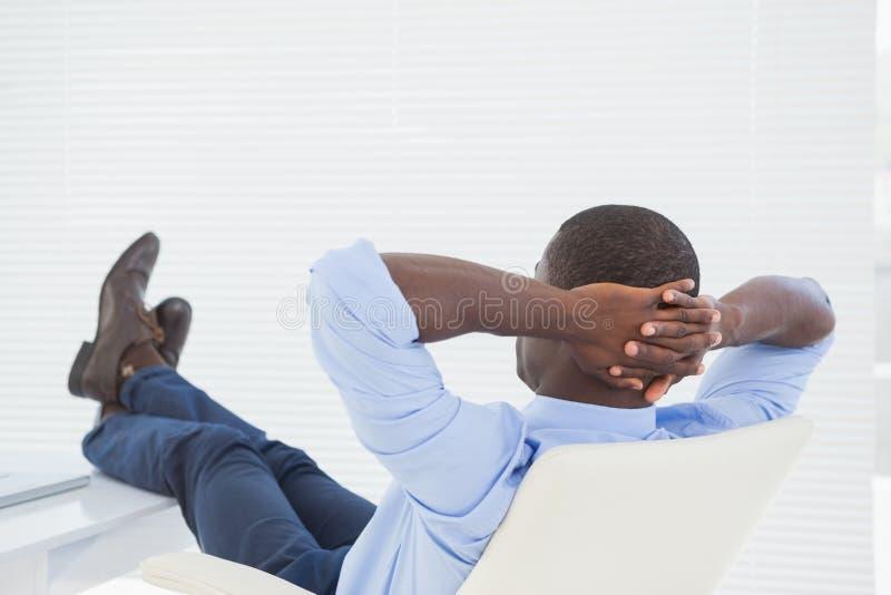 Χαλαρωμένος επιχειρηματίας με τα πόδια του επάνω στοκ φωτογραφία
