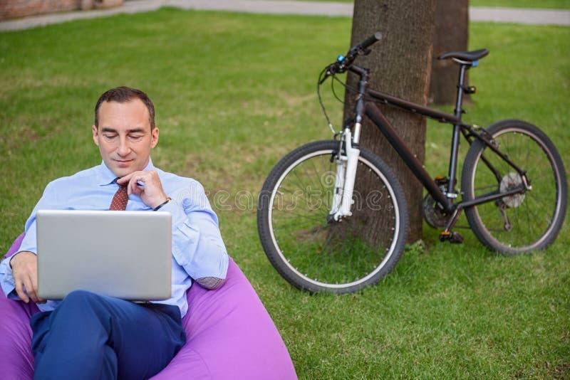 Χαλαρωμένος επιχειρηματίας με τον υπολογιστή στη φύση στοκ εικόνες