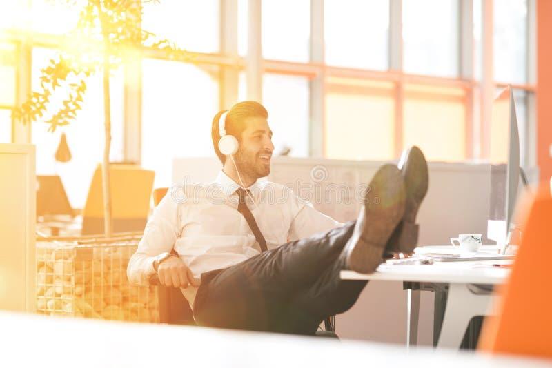Χαλαρωμένος νέος επιχειρηματίας πρώτα στον εργασιακό χώρο στα ξημερώματα στοκ φωτογραφίες με δικαίωμα ελεύθερης χρήσης