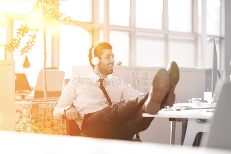 Χαλαρωμένος νέος επιχειρηματίας πρώτα στον εργασιακό χώρο στα ξημερώματα στοκ εικόνες