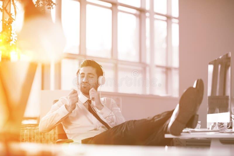 Χαλαρωμένος νέος επιχειρηματίας πρώτα στον εργασιακό χώρο στα ξημερώματα στοκ εικόνα