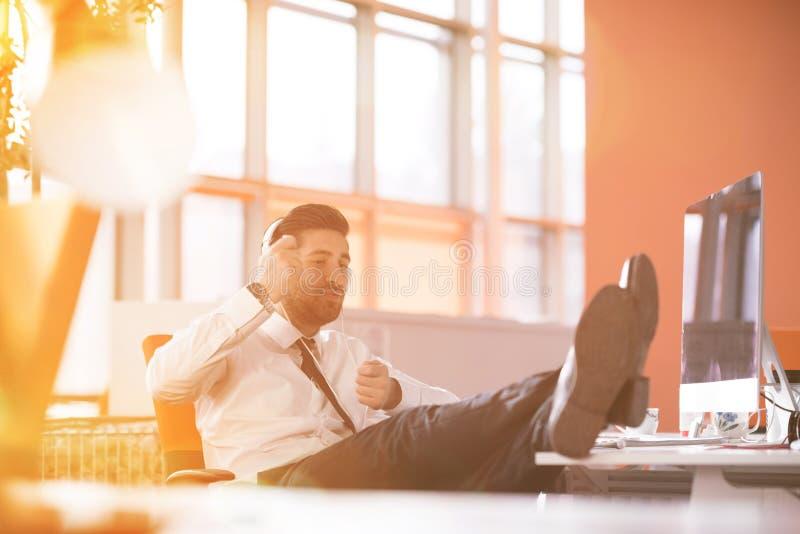 Χαλαρωμένος νέος επιχειρηματίας πρώτα στον εργασιακό χώρο στα ξημερώματα στοκ φωτογραφία