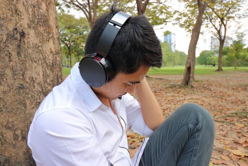 Χαλαρωμένος νεαρός άνδρας που ακούει τη μουσική με τα ακουστικά στο πάρκο πόλεων στοκ φωτογραφία