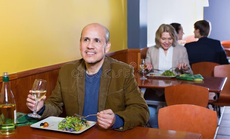 Χαλαρωμένος χαμογελώντας ανώτερος αρσενικός πελάτης με τα τρόφιμα και το κρασί στοκ εικόνα με δικαίωμα ελεύθερης χρήσης