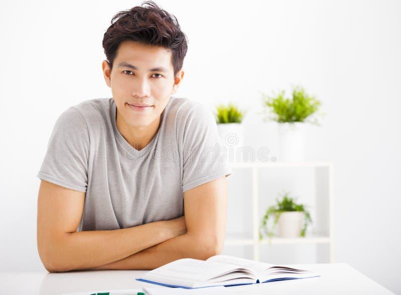Χαλαρωμένο βιβλίο ανάγνωσης νεαρών άνδρων στο καθιστικό στοκ εικόνα