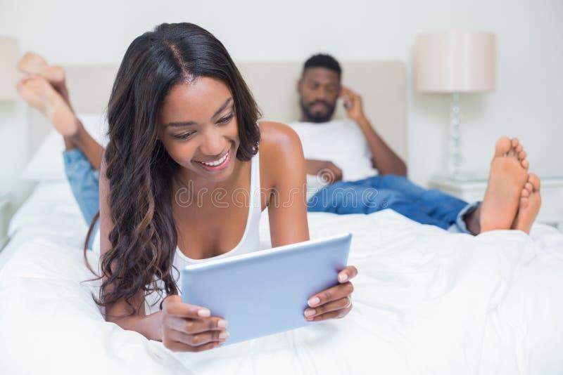 Χαλαρωμένο ζεύγος που χρησιμοποιεί την τεχνολογία στο κρεβάτι στοκ φωτογραφίες
