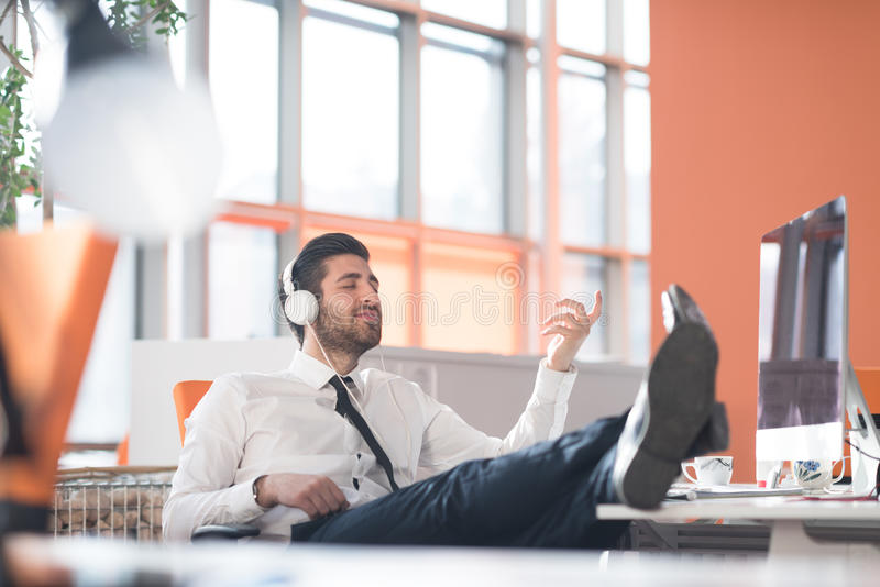 Χαλαρωμένο νέο επιχειρησιακό άτομο στο γραφείο στοκ εικόνα