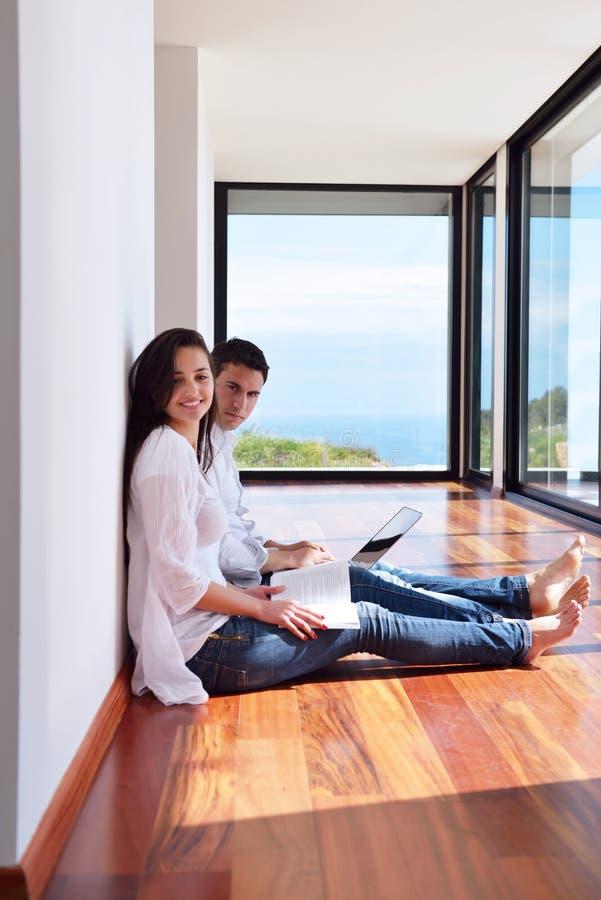 Χαλαρωμένο νέο ζεύγος που εργάζεται στο φορητό προσωπικό υπολογιστή στο σπίτι στοκ φωτογραφίες με δικαίωμα ελεύθερης χρήσης