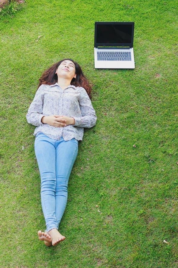 Χαλαρωμένο νεαρό άτομο (έφηβη) που βρίσκεται στη χλόη στοκ εικόνα με δικαίωμα ελεύθερης χρήσης