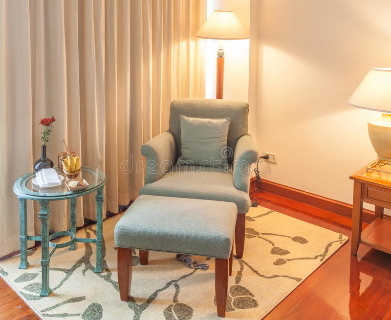 Χαλαρώνοντας γωνία, πολυθρόνα ξαπλώματος, Οθωμανός και πίνακας στο ξενοδοχείο στοκ εικόνα