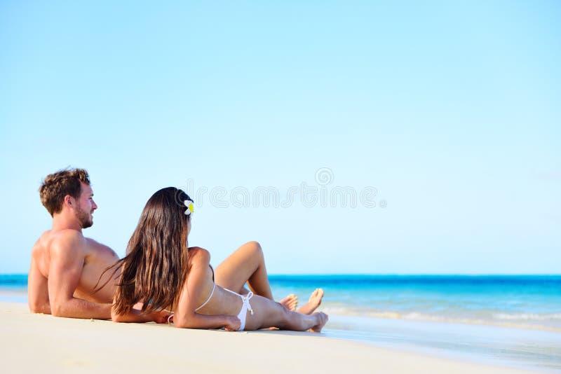Χαλαρώνοντας μαύρισμα ζευγών διακοπών παραλιών το καλοκαίρι στοκ φωτογραφία με δικαίωμα ελεύθερης χρήσης