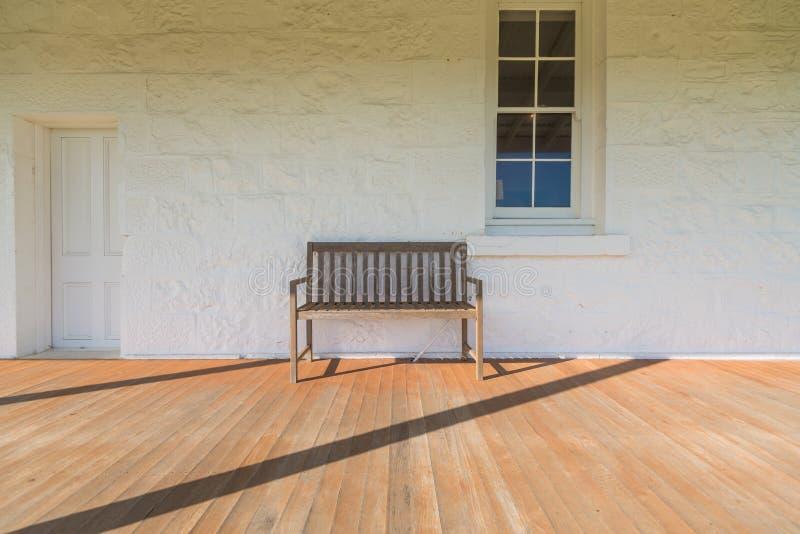 Χαλαρώστε την καρέκλα με το παράθυρο τουβλότοιχος και τον τρύγο πορτών στοκ φωτογραφίες με δικαίωμα ελεύθερης χρήσης