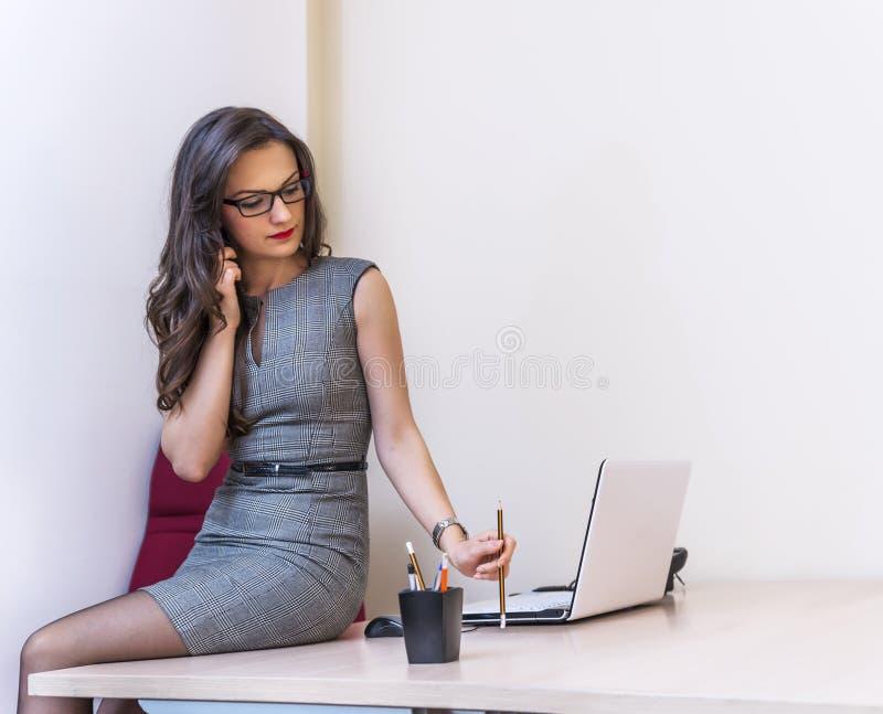 Χαλαρώστε την ομιλία επιχειρησιακών γυναικών στο τηλέφωνο και τη χρησιμοποίηση του lap-top της στοκ φωτογραφίες