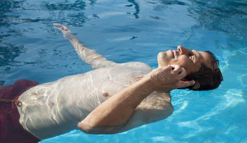 Χαλαρώστε τον επιχειρηματία χρησιμοποιώντας το τηλέφωνο από την πισίνα στοκ εικόνες με δικαίωμα ελεύθερης χρήσης