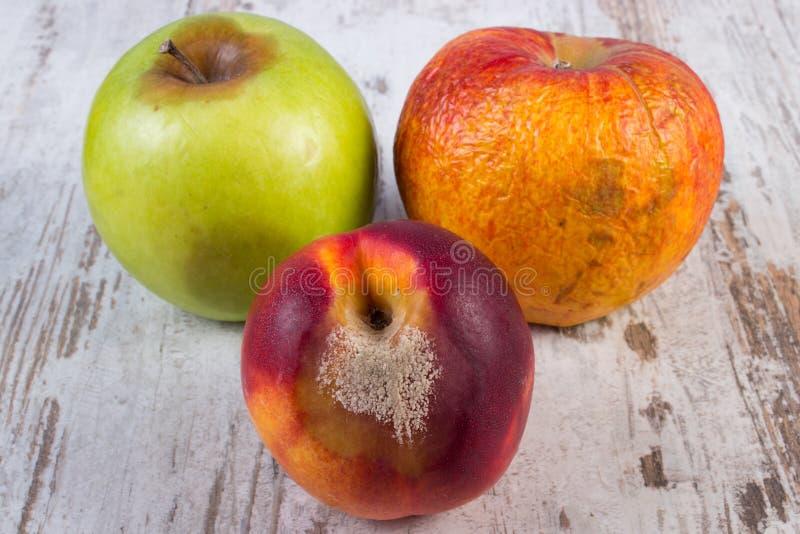 Χαλασμένα ροδάκινο και μήλο στον παλαιό ξύλινο άσπρο πίνακα στοκ φωτογραφία με δικαίωμα ελεύθερης χρήσης