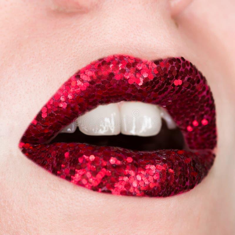 Χείλια που καλύπτονται κόκκινα με τα σπινθηρίσματα Όμορφη γυναίκα με το κόκκινο κραγιόν στα χείλια της, ανοικτό στόμα, καλλυντικά στοκ φωτογραφία με δικαίωμα ελεύθερης χρήσης