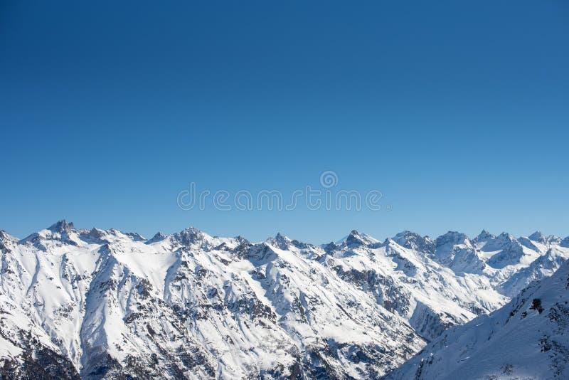 Χειμερινά βουνά με το χιόνι και το μπλε ουρανό στη συμπαθητική ημέρα ήλιων Χιονοδρομικό κέντρο, αθλητική έννοια Βουνά Καύκασου, π στοκ φωτογραφία με δικαίωμα ελεύθερης χρήσης
