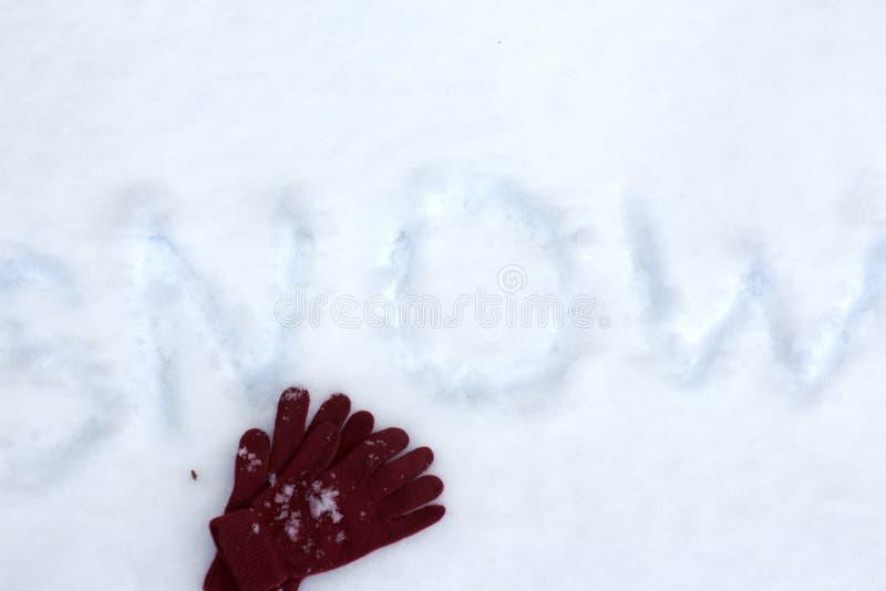 Χειμερινά γάντια στο χιόνι με την επιγραφή χιονιού Επίπεδος βάλτε τη λαμπρή σύσταση στοκ εικόνες με δικαίωμα ελεύθερης χρήσης