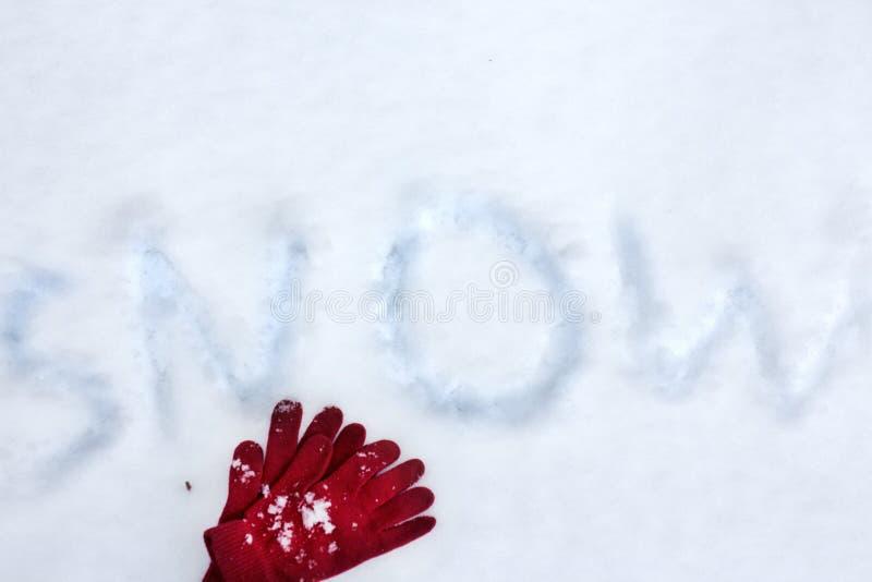 Χειμερινά γάντια στο χιόνι με την επιγραφή χιονιού Επίπεδος βάλτε τη λαμπρή σύσταση στοκ φωτογραφία