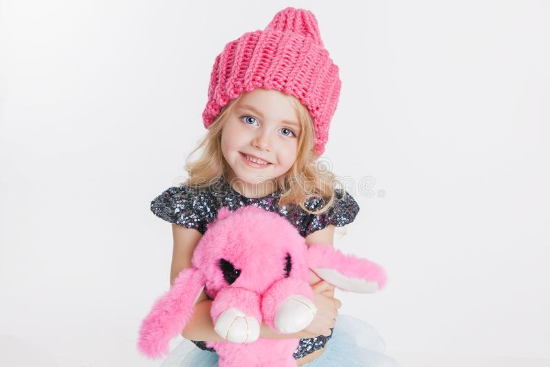 Χειμερινά ενδύματα Πορτρέτο λίγου σγουρού κοριτσιού στο πλεκτό ρόδινο χειμερινό καπέλο στο λευκό Ρόδινο παιχνίδι κουνελιών στα χέ στοκ εικόνα με δικαίωμα ελεύθερης χρήσης