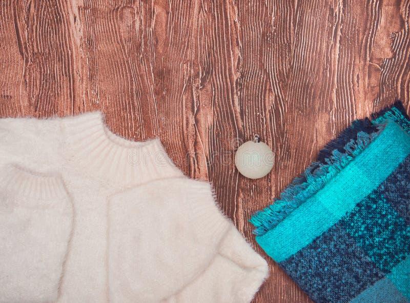 Χειμερινά ενδύματα Όμορφη ελαφριά γυναικεία μόδα σε ένα ξύλινο υπόβαθρο στοκ φωτογραφίες