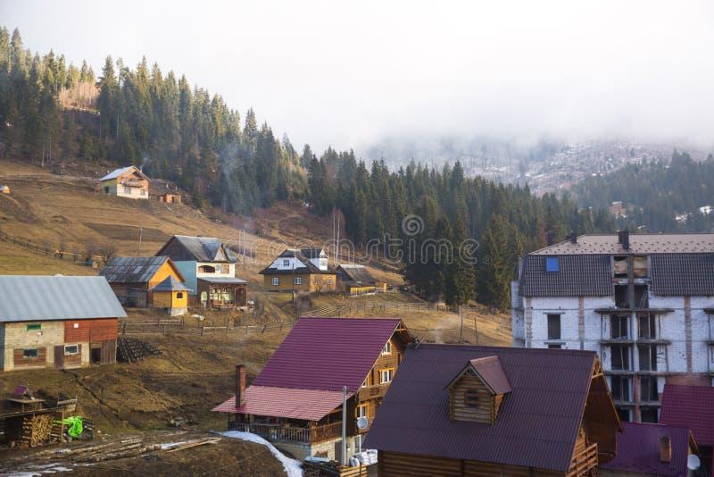 Χειμερινή άποψη του χειμερινού χιονοδρομικού κέντρου με τα σπίτια, τα εξοχικά σπίτια και τα ξύλα στοκ φωτογραφίες