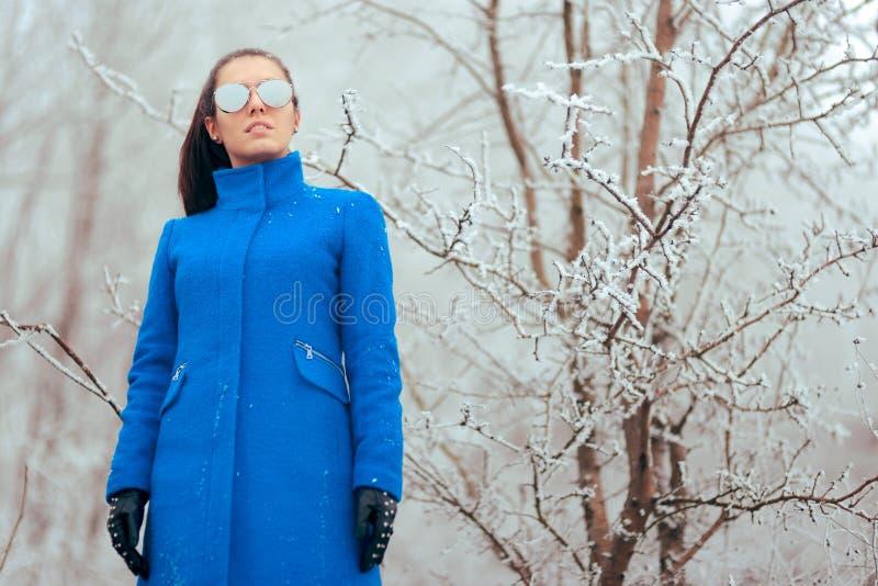 Χειμερινή γυναίκα μόδας με τα γυαλιά ηλίου καθρεφτών και το μπλε παλτό στοκ εικόνα
