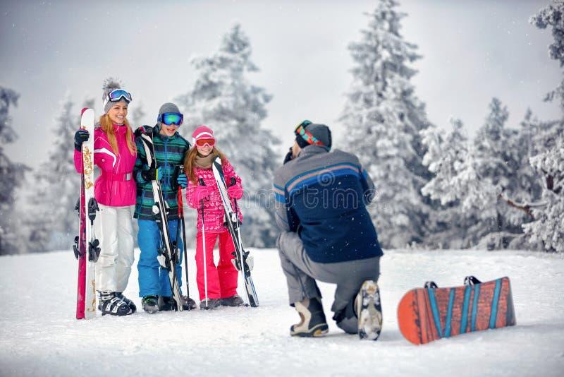 Χειμερινή εποχή - ο πατέρας παίρνει να φωτογραφίσει την οικογένεια στις διακοπές μέσα στοκ φωτογραφίες