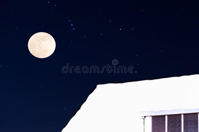 Χειμερινή εποχή τη νύχτα, μια στέγη που καλύπτονται σε ένα παχύ στρώμα του χιονιού με τα αστέρια και μια πανσέληνος, υπόβαθρο Χρι στοκ φωτογραφία