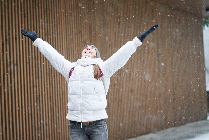 Χειμερινή ώρα Νεαρή χαρούμενη καυκάσια κοπέλα με λευκό μπουφάν που απολαμβάνει το πρώτο χιόνι με σηκωμένα χέρια στοκ φωτογραφίες με δικαίωμα ελεύθερης χρήσης