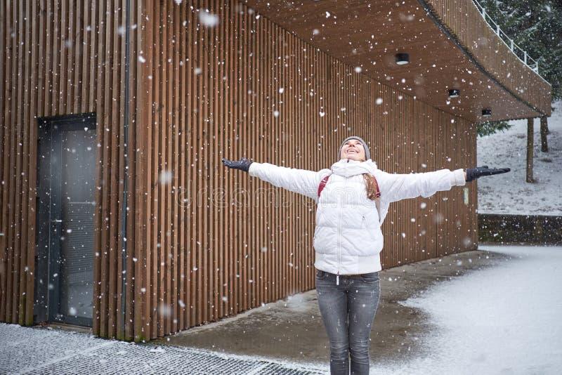 Χειμερινή ώρα Πρώτο χιόνι Ένα νεαρό όμορφο χαρούμενο κορίτσι που απολαμβάνει χιονόπτωση στοκ φωτογραφία