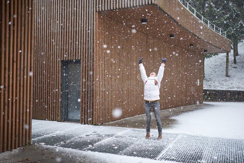 Χειμερινή ώρα Πρώτο χιόνι Ένα νεαρό όμορφο χαρούμενο κορίτσι που απολαμβάνει χιονόπτωση στοκ εικόνες
