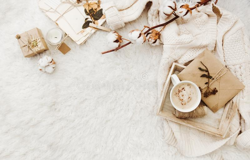 Χειμερινό άνετο υπόβαθρο με το φλιτζάνι του καφέ, το θερμό πουλόβερ και τις παλαιές επιστολές Επίπεδος βάλτε στοκ φωτογραφία