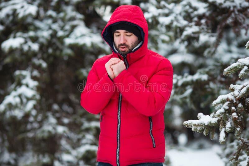 Χειμερινό αρσενικό πορτρέτο Το νέο γενειοφόρο άτομο που προσπαθεί να θερμάνει το κρύο του παραδίδει το χειμερινό πάρκο παγετού κρ στοκ φωτογραφίες