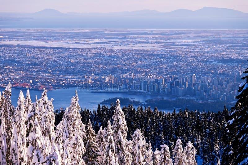 Χειμερινό ηλιοβασίλεμα στα βουνά πέρα από την πόλη στοκ εικόνες