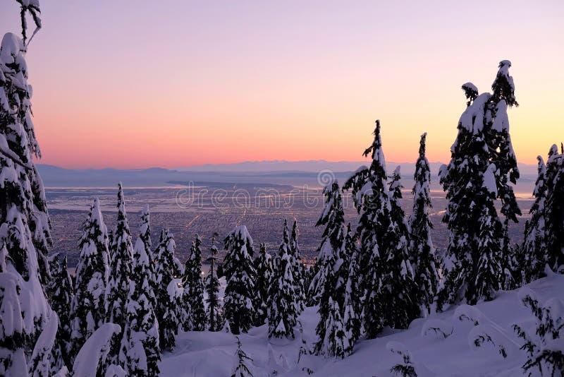 Χειμερινό ηλιοβασίλεμα στα βουνά πέρα από την πόλη στοκ εικόνα