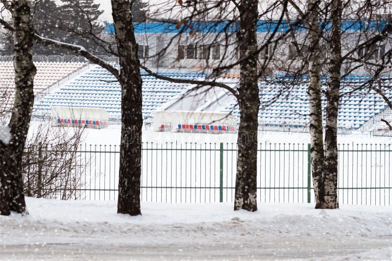 Χειμερινό κενό στάδιο Αγωνιστικός χώρος ποδοσφαίρου και καθίσματα για τους θεατές ομάδων που καλύπτονται με το χιόνι Αθλητικές επ στοκ εικόνα