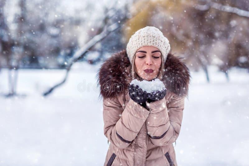 Χειμερινό κορίτσι Χριστουγέννων που φυσά το μαγικό χιόνι στο χέρι της Νεράιδα μπαζούκας στοκ εικόνα