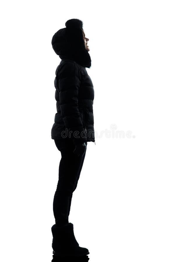 Χειμερινό παλτό γυναικών που φαίνεται σκιαγραφία επάνω χαμόγελου στοκ φωτογραφία με δικαίωμα ελεύθερης χρήσης