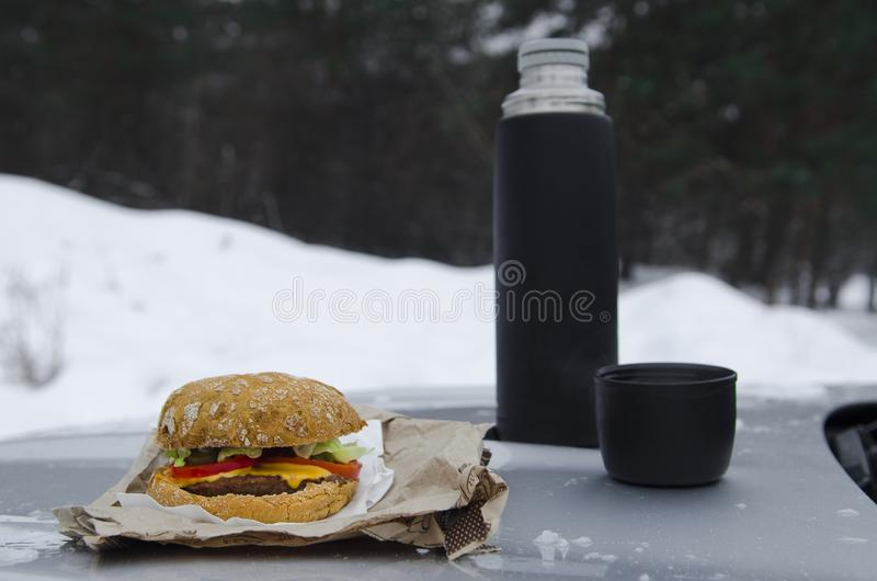Χειμερινό πικ-νίκ με το τσάι και burger στην κουκούλα ενός ασημένιου αυτοκινήτου στα πλαίσια του δάσους στοκ φωτογραφία με δικαίωμα ελεύθερης χρήσης