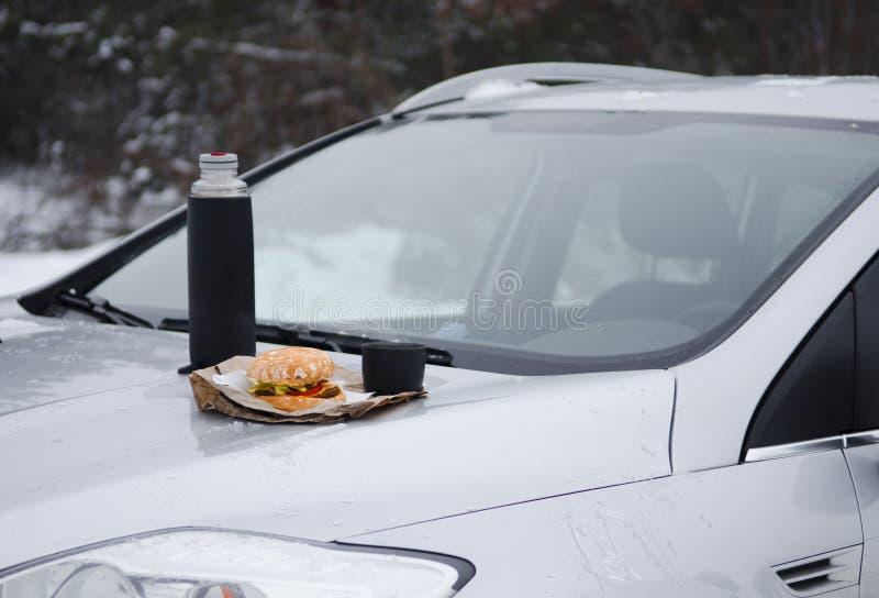 Χειμερινό πικ-νίκ με το τσάι και burger στην κουκούλα ενός ασημένιου αυτοκινήτου στα πλαίσια του δάσους στοκ φωτογραφίες