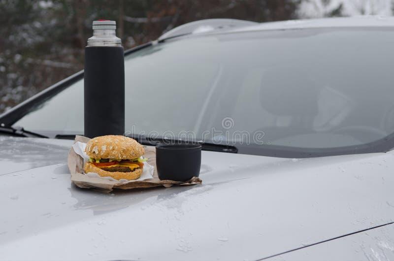 Χειμερινό πικ-νίκ με το τσάι και burger στην κουκούλα ενός ασημένιου αυτοκινήτου στα πλαίσια του δάσους στοκ εικόνες με δικαίωμα ελεύθερης χρήσης