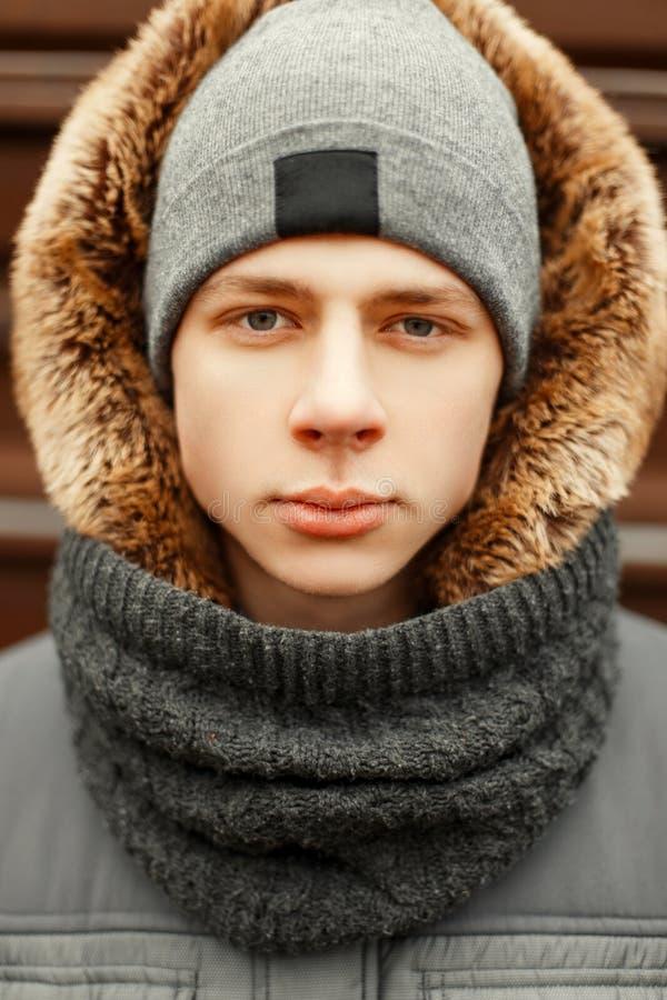 Χειμερινό πορτρέτο ενός νεαρού άνδρα σε ένα σακάκι χειμερινής μόδας στοκ εικόνες