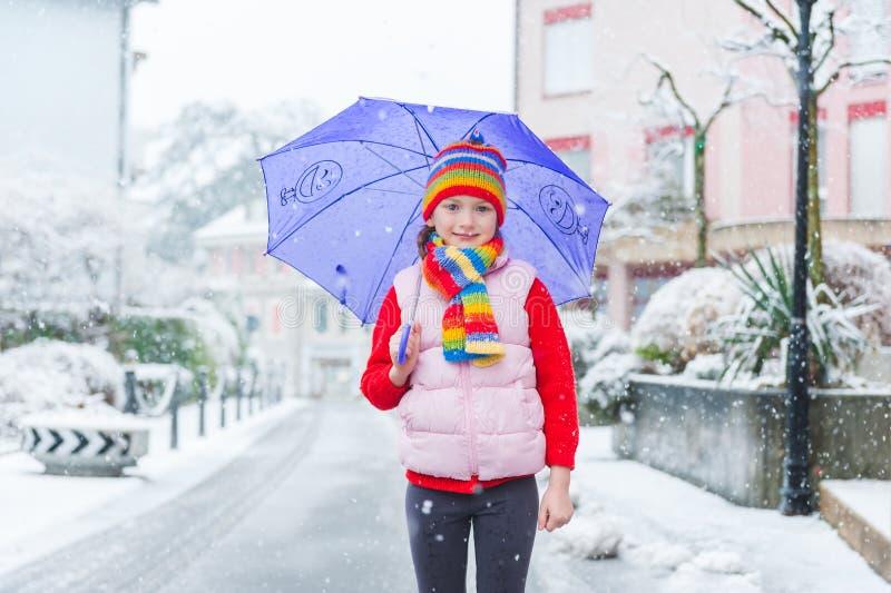 Χειμερινό πορτρέτο ενός χαριτωμένου μικρού κοριτσιού κάτω από τις χιονοπτώσεις στοκ εικόνες