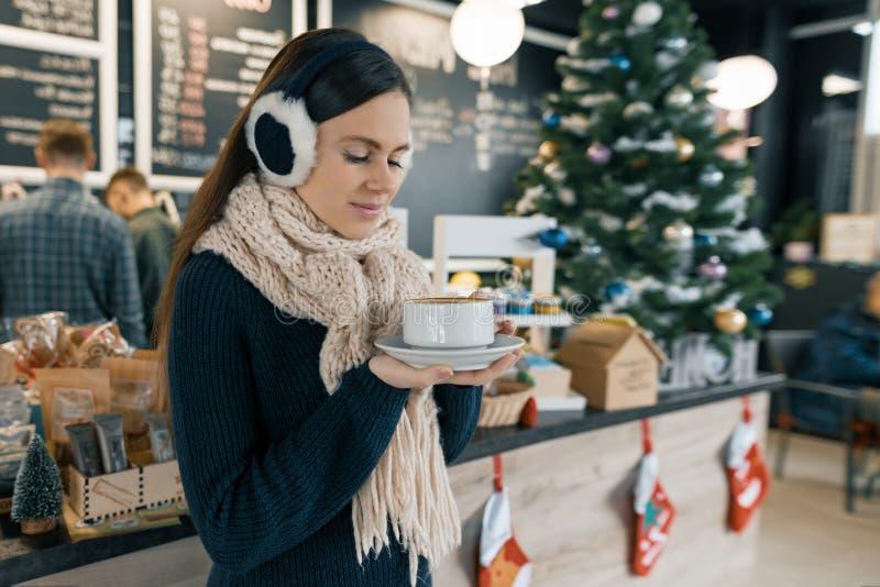 Χειμερινό πορτρέτο της νέας όμορφης γυναίκας στο πλεκτό μαντίλι, αυτιά γουνών, θερμό πουλόβερ με το φλιτζάνι του καφέ Κορίτσι κον στοκ φωτογραφία με δικαίωμα ελεύθερης χρήσης