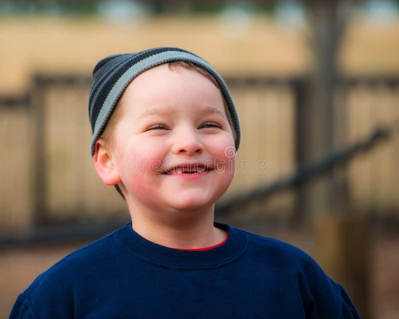 Χειμερινό πορτρέτο του ευτυχούς αγοριού στην παιδική χαρά στοκ φωτογραφίες