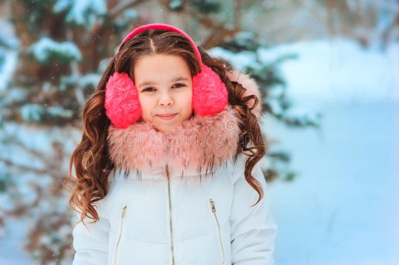 Χειμερινό πορτρέτο του ευτυχούς κοριτσιού παιδιών στο ρόδινο περπάτημα καλυμμάτων αυτιών υπαίθριο στο χιονώδες χειμερινό δάσος στοκ εικόνες
