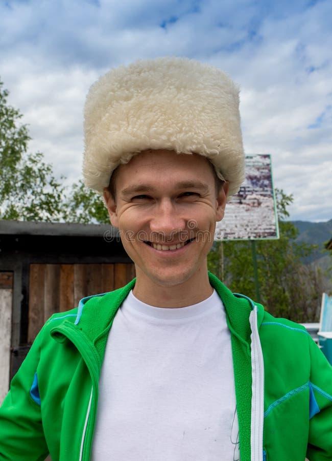 Χειμερινό πορτρέτο του ευτυχούς νεαρού άνδρα που χαμογελά στο καπέλο στοκ φωτογραφία με δικαίωμα ελεύθερης χρήσης