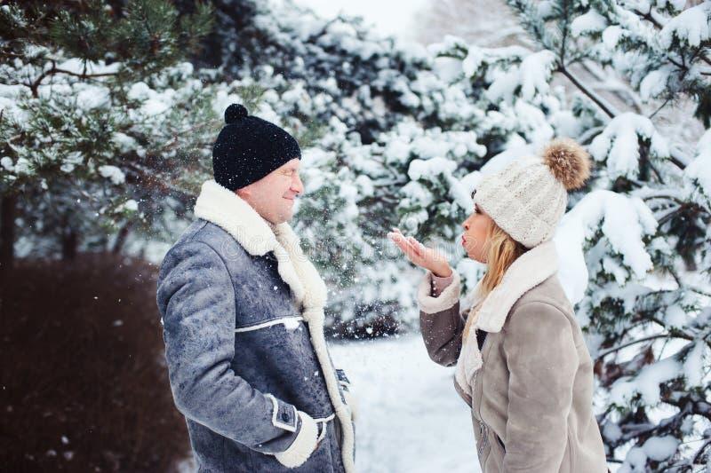 χειμερινό πορτρέτο του ευτυχούς παίζοντας ζευγών, φυσώντας χιονιού και καλημέρα εξόδων υπαίθριων στο χιονώδες δάσος στοκ φωτογραφία