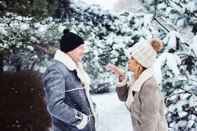 χειμερινό πορτρέτο του ευτυχούς παίζοντας ζευγών, φυσώντας χιονιού και καλημέρα εξόδων υπαίθριων στοκ εικόνες